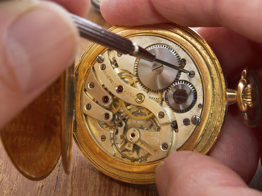 mechanism of a pocket watch timepiece being repaired